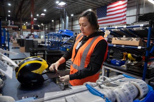 Xenith employee Garcia Esperanza assembles a University of Michigan football helmet during a facility tour back in 2019.