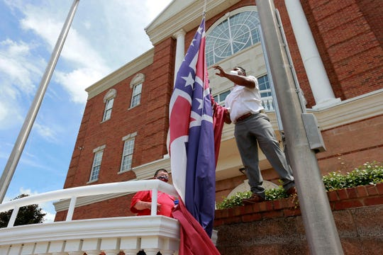 City of Tupelo Community Outreach Coordinator Marcus Gary takes down the Mississippi state flag that flew over the City Hall of Tupelo one last time Monday. Mississippi is retiring the last state flag in the U.S. that includes the Confederate battle emblem.
