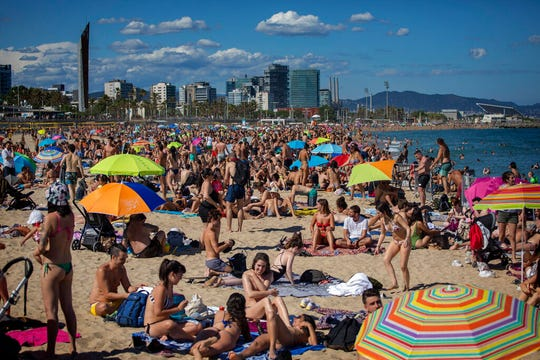 In this Saturday, June 13, 2020 file photo, people enjoy the warm weather on the beach in Barcelona, Spain.