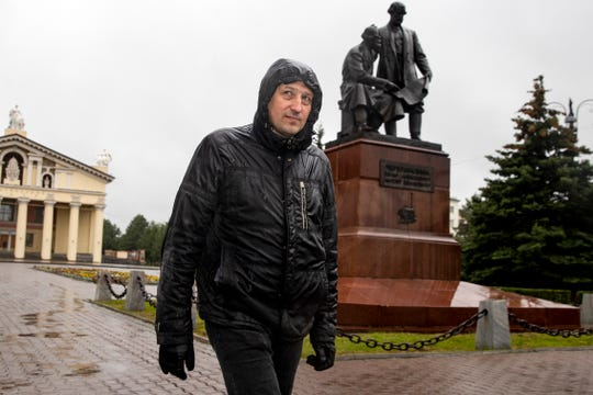 In this photo taken on Sunday, June 28, 2020, Nikolay Nemytov, a 43-year-old worker at Russian Railways, walks past a monument to local inventors and engineers.