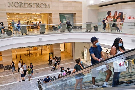 In this Monday, June 29, 2020 file photo, shoppers move about in Garden State Plaza in Paramus, N.J. U.S. consumer confidence rose in June, reflecting the partial re-opening of the country but the concern is that rising coronavirus cases in many states could jeopardize future gains.