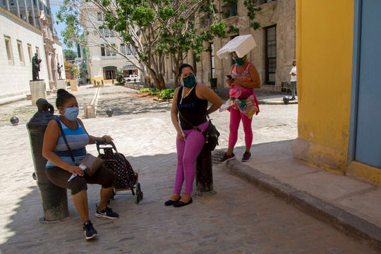 Women wearing masks to curb the spread of the new coronavirus chat on a corner in Old Havana, one using a piece of styrofoam to shade herself, in Havana, Cuba, Tuesday, June 23, 2020.