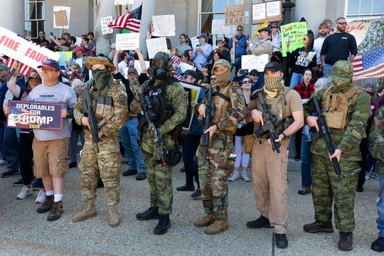 """In this May 2, 2020, file photo, people, including those with the boogaloo movement, demonstrate against business closures due to concern about COVID-19, at the State House in Concord, N.H. Facebook says it is banning a """"U.S.-based anti-government network"""" associated with the broader """"boogaloo"""" movement, designating it as a dangerous organization similar to groups like ISIS and white supremacist groups and individuals already banned from its service."""