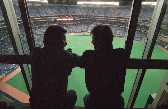 Spectators look out at the field of the SkyDome in Toronto, from a window of the SkyDome Hotel before Game 5 of the World Series between the Toronto Blue Jays and the Atlanta Braves.