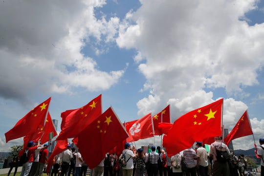Pro-China supporters hold Chinese and Hong Kong national flags during a rally to celebrate the approval of a national security law for Hong Kong, in Hong Kong, Tuesday.