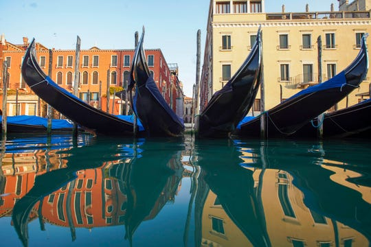 In this Monday, April 6, 2020 file photo, moored gondolas are reflected on the water of the Gran Canal, in Venice. The European Union announced Tuesday, June 30, 2020 that it will reopen its borders to travelers from 14 countries, but most Americans have been refused entry for at least another two weeks due to soaring coronavirus infections in the U.S.