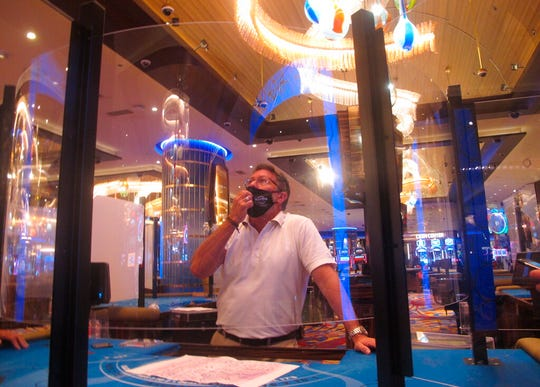 In this June 24, 2020 photo, Joe Lupo, president of the Hard Rock casino in Atlantic City N.J. examines the installation of protective barriers being installed at a card table on the casino floor.