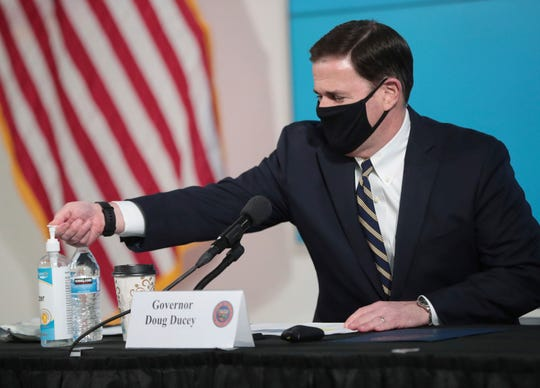 Arizona Gov. Doug Ducey uses hand sanitizer before updating reporters on COVID-19 in the state Monday in Phoenix.