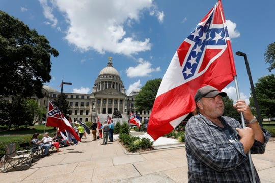 """David Flynt of Hattiesburg stands outside the state Capitol with other current Mississippi flag supporters in Jackson, Miss. on Sunday, June 28. """"I love this flag,"""" Flynt said."""