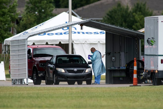 People take COVID-19 tests at the Deaconess Clinic drive-through testing site located near Lynch and North Green River Roads in Evansville, Ind., Tuesday, June 30, 2020.
