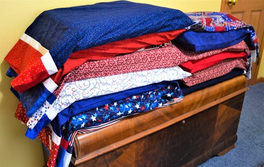 Stacks of quilts, handmade by the Grateful Valor Girls, sit at Jill Bothe's Port Clinton home. The group wants to award the quilts to local veterans who have been touched by war.