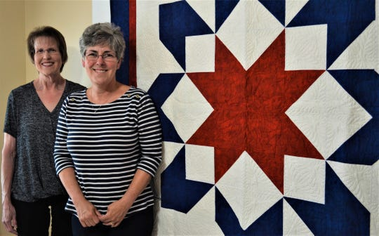 "Jill Bothe, left, and Mary Gill stand next to one of the many quilts handmade by the Grateful Valor Girls, the local chapter of the national Quilts of Valor Foundation.  The custom stitching, including eagle in the center, was stitched by ""longarmer"" Cathi Dix of Huron, who donated her time for the group."