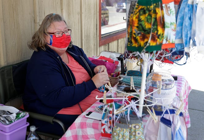 Sandy Nimmo, owner of SENsational handcrafts, makes free face masks outside her store on June 12, 2020, in Sturgeon Bay, Wis.