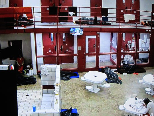 Security cameras in R-pod at the Cascade County Detention Center show inmates sleeping on floor mats in walkways and communal spaces.