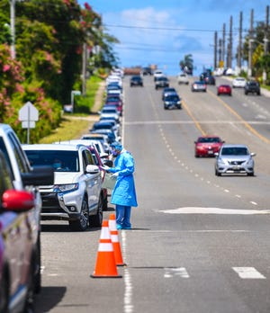A Department of Public Health and Social Services worker prescreens one of the many vehicles lined up on the shoulder of Route 10 in Mangilao for COVID-19 testing in this file photo from June taken near the Santa Teresita Catholic Church.