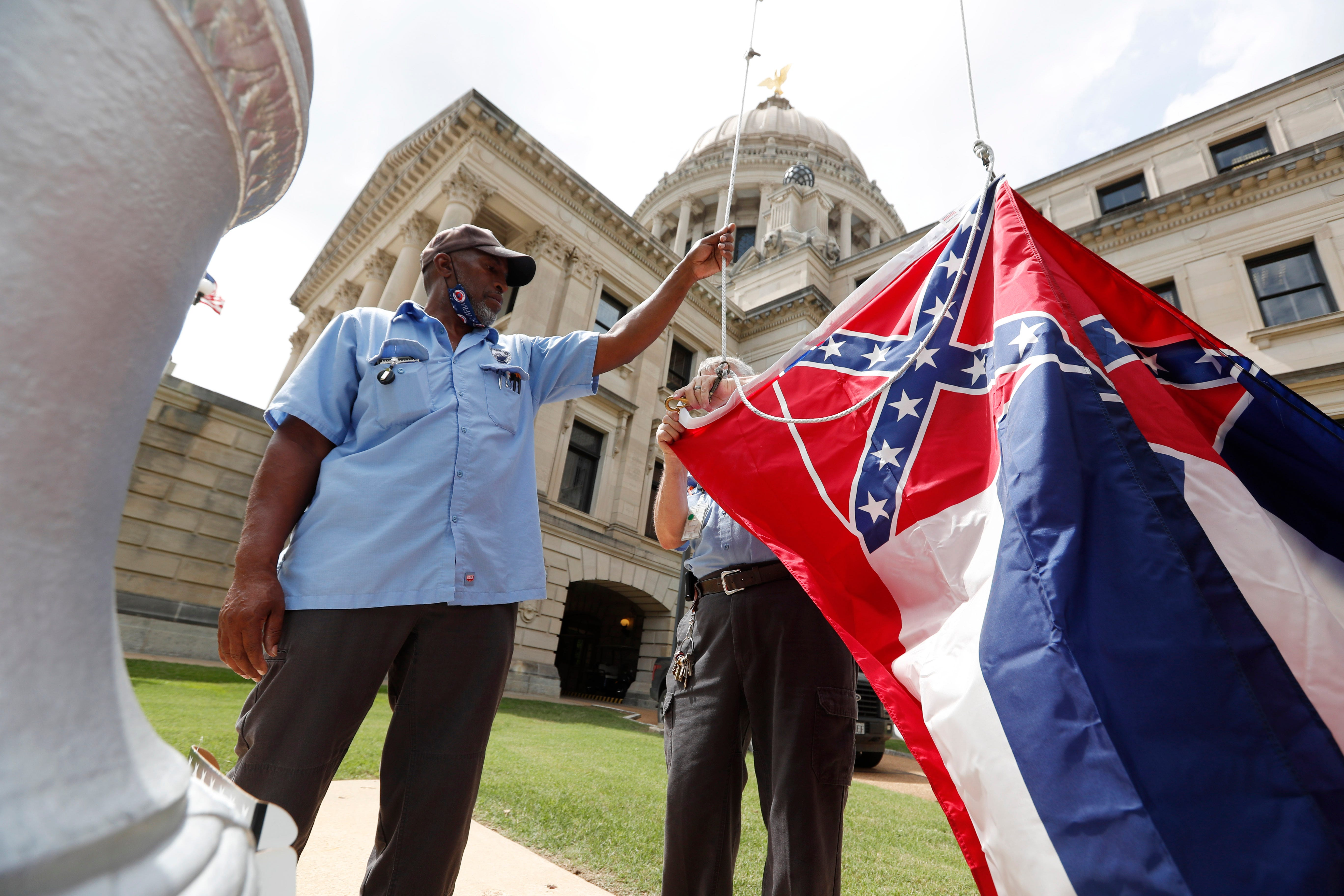 Mississippi Department of Finance and Administration employees Willie Townsend, left, and Joe Brown attach a state flag to the harness before raising it over the Capitol grounds in Jackson, Miss., on June 30. The two men raised about 100 flags, provided by the Secretary of State's office, for people or organizations that purchased a state flag that flew over the grounds. The state flag was altered in 1894 to feature the Confederate battle flag. Voters in November will decide on a new flag.