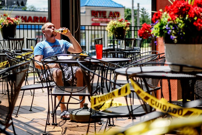 Cody Turner, of DeWItt, enjoys a lunch outside on the patio at El Azteco on Tuesday, June 30, 2020, in Lansing. Caution tape surrounds tables that are not in use in compliance with COVID-19 restrictions.