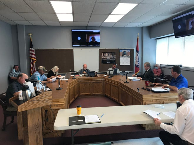 Members of the Ozark Mountain Solid Waste District's Board of Directors meets Monday in Harrison. The board voted unanimously to not appeal a string of recent circuit court decisions that found the district's yearly $18 service fee to be unconstitutional.