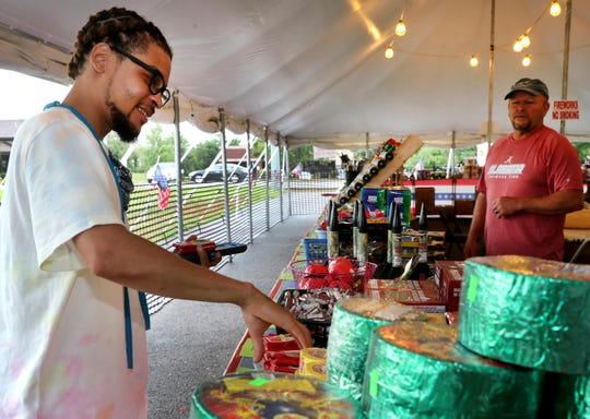 Tyree Hill, left, picks up a few packs of fireworks at the Titan Fireworks tent off Veterans Parkway in Murfreesboro on Monday, June 29, 2020, as Gary Field helps Hill find what he is looking for.