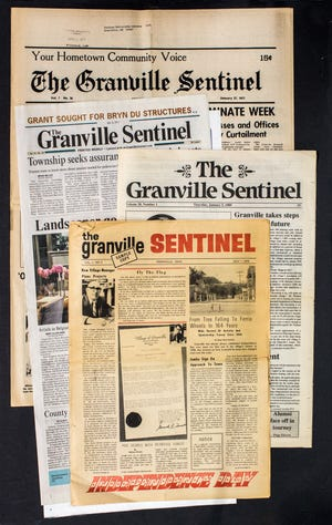 One of the first issues of The Granville Sentinel (foreground) is contrasted with the newspaper's look in later years.
