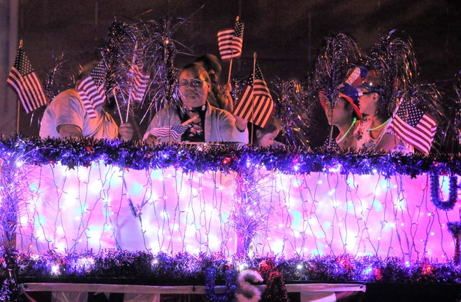 Riders on a float wave to the crowd during the 2019 Electric Light Parade in downtown Farmington.