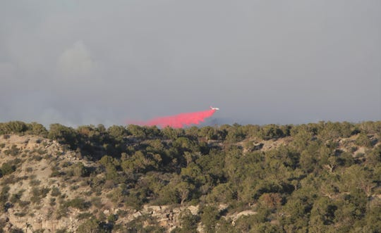 An air tanker drops fire retardant on the Wood Springs 2 fire, burning east of Nazlini, Arizona, on June 29.