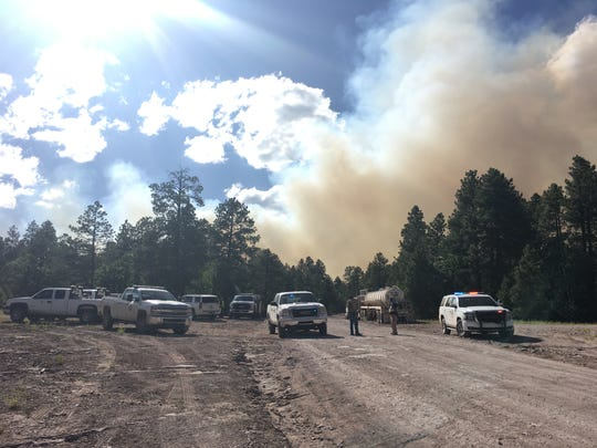 Rangers from the Navajo Department of Fish and Wildlife manage a roadblock on Navajo Route 7 in Sawmill, Arizona on June 29. Smoke from the Wood Springs 2 fire is pictured in the background.