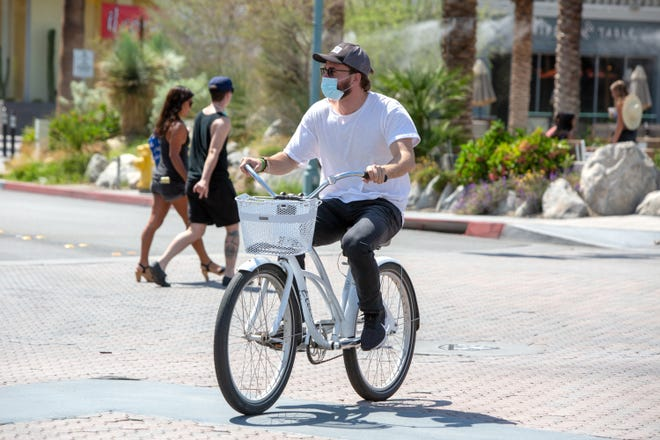 A cyclist dons a mask while riding along Palm Canyon Drive in Palm Springs, Calif., on Saturday, June 27, 2020. Face coverings are required in most indoor and outdoor settings in California to slow the spread of COVID-19.