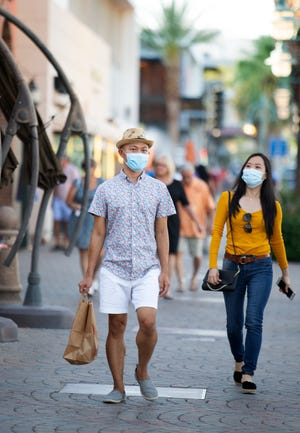 People don masks while walking along Palm Canyon Drive in Palm Springs over the weekend. Health officials ordered bars shut down again, effective Tuesday, as cases of coronavirus spiked.