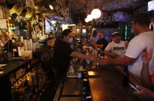 Matthew Rendon serves last-call after a Gov. Doug Ducey ordered 8 p.m. shutdown of bars, nightclubs, pools, waterparks and tubing in Scottsdale on June 29, 2020.