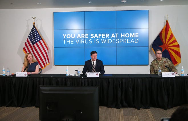 Gov. Doug Ducey (center) along with Dr. Cara Christ (left) and Maj. General Michael McGuire field questions from reporters on COVID-19 during a news conference in Phoenix on June 29, 2020. Gov. Ducey ordered the closing of bars, gyms, theaters, waterparks and tubing.