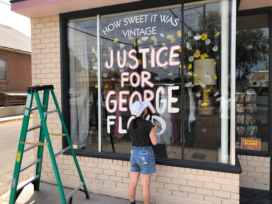 """Crissy Burgstaler paints her storefront window with """"Justice for George Floyd,"""" May 31, 2020."""