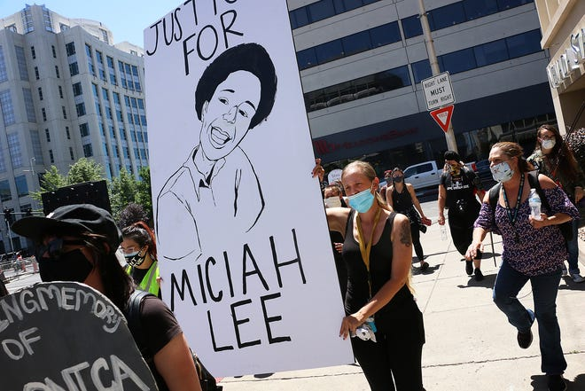 Miciah Lee's mother Susan Clopp carries a sign for her son during a Black Lives Matter rally in Reno on June 26, 2020.
