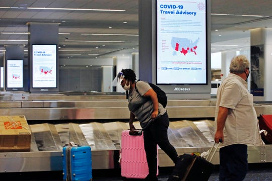 An arriving passenger wearing a face shield, left, collects her luggage in the baggage claim area of LaGuardia Airport's Terminal B, Thursday, June 25, 2020, in New York. New York, Connecticut and New Jersey are asking visitors from states with high coronavirus infection rates to quarantine for 14 days.