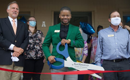 Javin Mitchell, center with the San Angelo branch of Texas Home Health, prepares to cut the ribbon during a ceremony Tuesday, June 30, 2020.