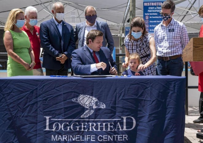 Gov. Ron DeSantis, center, asks his daughter Madison with first lady Casey DeSantis, to hand out markers for the signing of two bills related to protecting the state's environment at the Loggerhead Marinelife Center in Juno Beach.