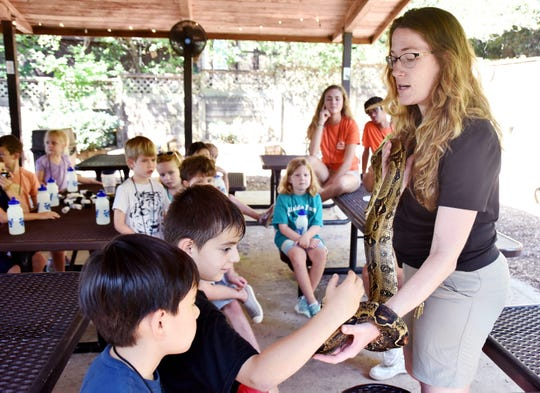 Jennifer Garcia, right, education program coordinatior at the Greenville Zoo talks holds a red tail boa constrictor  while talking to a group in a day camp.