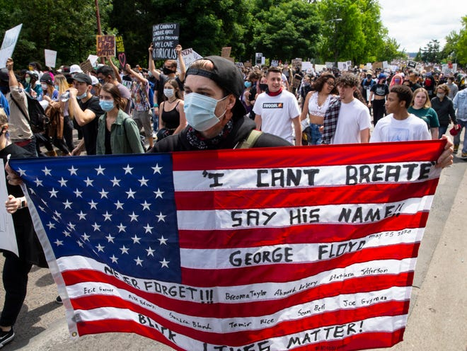 Marchers join a Black Lives Matter rally in Eugene, Ore., on May 31. Other protesters have held the flag upside down, a signal of distress.