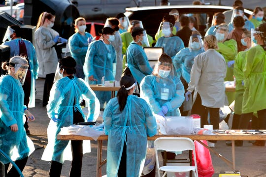 Medical personnel prepare to test hundreds of people lined up in vehicles in Phoenix on June 27, 2020.