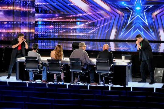 The Brothers Gage play their harmonicas for 'America's Got Talent' judges Simon Cowell, left with back to camera, Sofia Vergara, Eric Stonestreet and Howie Mandel and a sea of empty seats.