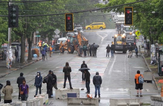Protesters gather a block away as Seattle Department of Transportation workers remove barricades at the intersection of 10th Avenue and Pine Street June 30 in Seattle.