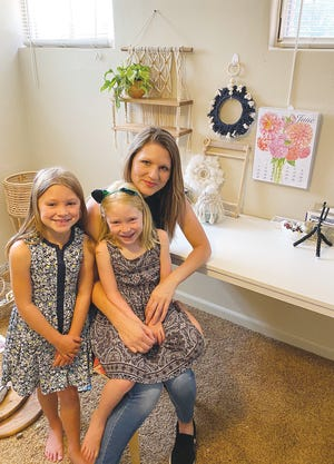 EZB Creations artist Emmalee Zeelie with daughters Yanika, 6, and Esmé, almost 5, pose with EZB Creations macramé wall hangings in the background. Zeelie  sells her work through Market 54 and Giesen Greenhouse in Pratt and online through her EZB Creations Facebook site and also through Instagram.