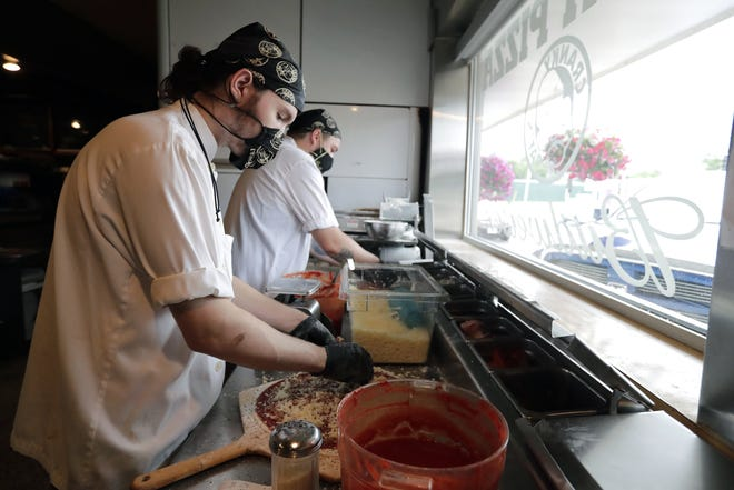Cranky Pat's Pizza employees Devon Tesch, left, and Michael Tom wear masks while they make pizzas in Neenah.