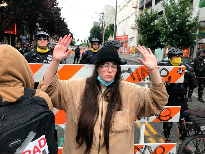 A protester stands with her hand up in front of a road blocked by Seattle police in the Capitol Hill Organized Protest zone early Wednesday, July 1, 2020.