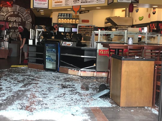 Damage at a Jimmy John's is seen after a vehicle crashed through the front doors.