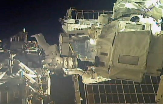 In this image taken from NASA video, commander Chris Cassidy, right, and NASA astronaut Bob Behnken perform their second spacewalk in under a week Wednesday, July 1, 2020, to replace old batteries outside the International Space Station.