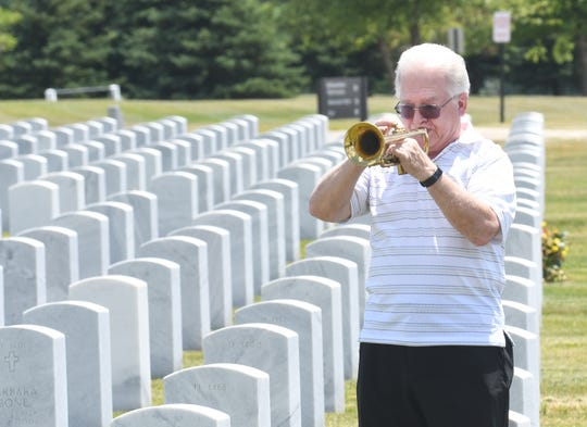 Vietnam veteran Andrew Pietrzyk, on vacation from Florida with his wife Carolann Pietrzyk, (not shown) plays taps to pay respects to friend, family doctor and fellow veteran Roy W. Matthews Jr. at the Great Lakes National Cemetery in Holly, Michigan on Wednesday.