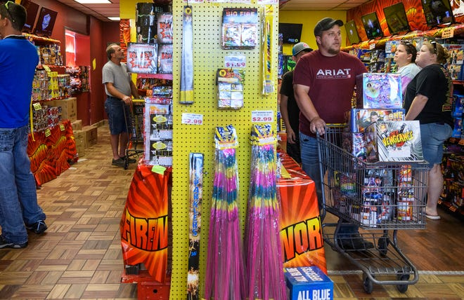 Justin Wininger, center, pushes a cart full of fireworks to the checkout counter at Dreamland Fireworks, located near the intersection of Diamond Avenue and Stringtown Road, in Evansville, Ind., Wednesday afternoon, July 1, 2020. The fireworks store had to unload three trucks worth of fireworks inventory Wednesday as they worked to keep the shelves stocked for people preparing for the upcoming Fourth of July holiday.