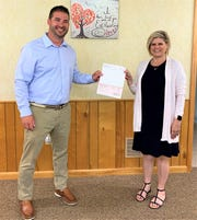 Derek Sprouse, of Sprouse Insurance presentes a check to Toni Brubaker, Director of Heartbeat.