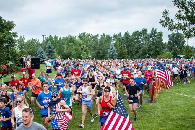 Runners in a recent Loveland Liberty 5K take off from the starting line at Fairgrounds Park. Participants will start in waves of no more than 50 runners apiece, 30 minutes apart, in this year's event Saturday to comply with coronavirus restrictions.